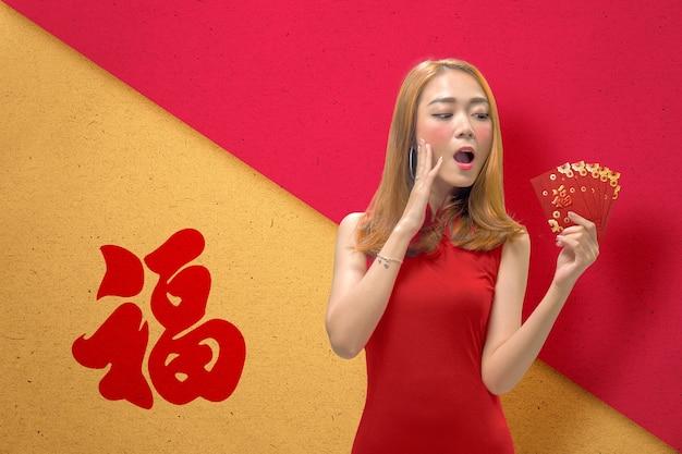 赤い封筒を保持しているチャイナドレスのアジアの中国人女性。旧正月おめでとう