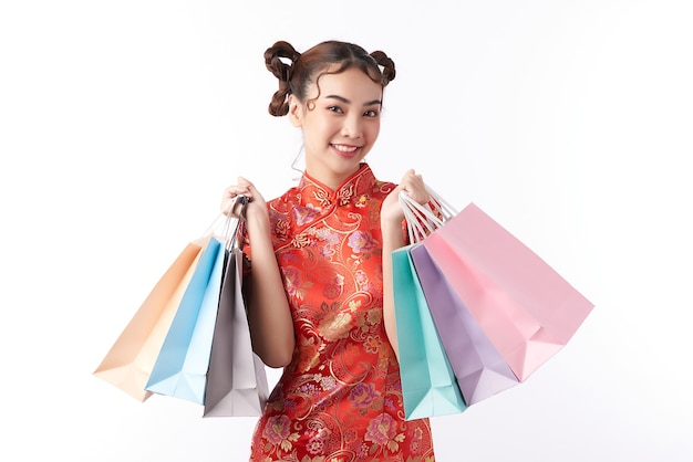 ショッピングバッグと伝統的なドレスのアジアの中国人女性。中国の旧正月祭り。