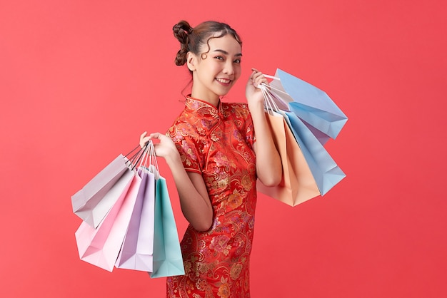 Asian chinese woman in traditional dress on red background with shopping bags. chinese new year festival.