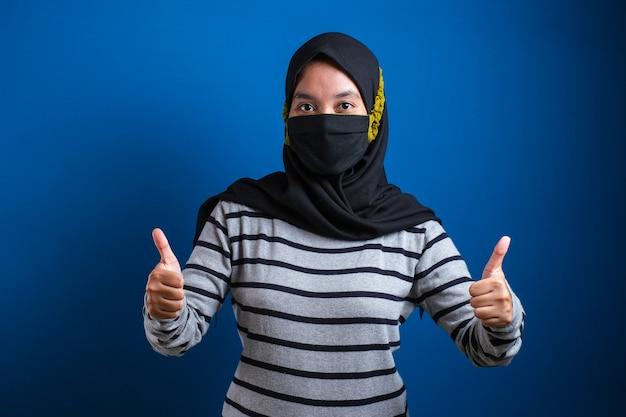 아시아 대학생 소녀는 학교에 돌아오는 동안 파란색 배경에 코로나 바이러스가 퍼지는 것을 방지하기 위해 엄지손가락을 치켜들고 마스크를 착용합니다.
