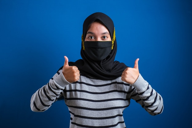 Asian college student girl thumb up and wearing masks to prevent the spread of corona virus against blue background while back to school.