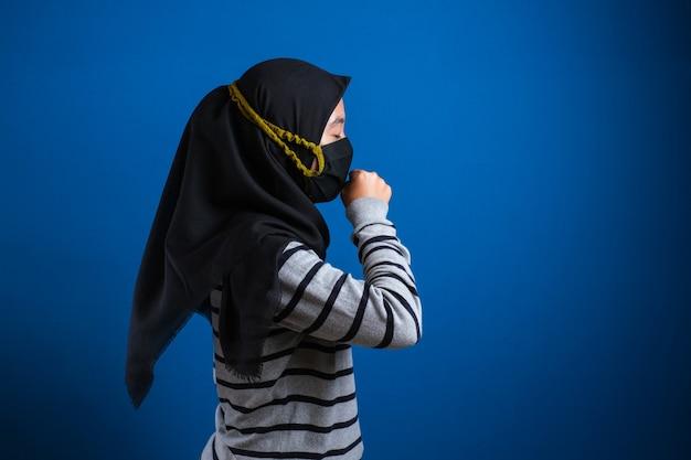 마스크를 쓴 아시아 대학생 여학생이 손으로 입을 막으면서 기침을 하고 있다. 그녀는 몸이 좋지 않다. 코로나 바이러스 질병의 증상