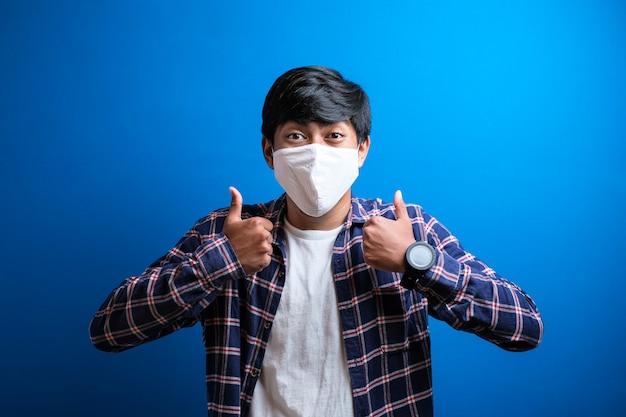 アジアの大学生の男性は、学校に戻っている間、青い背景にコロナウイルスが広がるのを防ぐために親指を立ててマスクを着用しています。