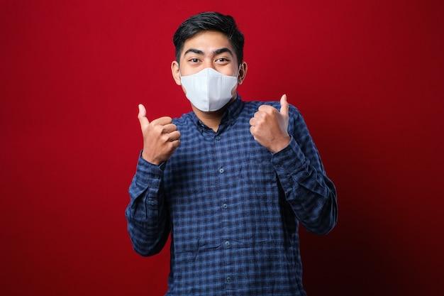 アジアの大学生の男性は、学校に戻っている間、赤い背景に対してコロナウイルスの拡散を防ぐために親指を立ててマスクを着用しています。