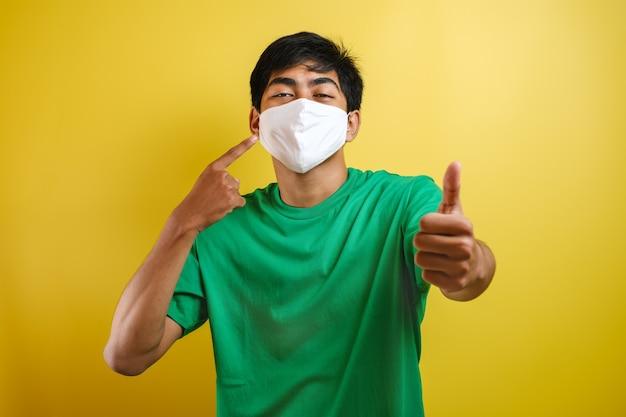 黄色の背景にコロナウイルスの拡散を防ぐために親指を立ててマスクを着用しているアジアの大学生の男性