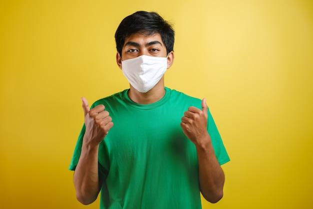 노란색 배경에 코로나 바이러스가 퍼지는 것을 막기 위해 아시아 대학생 남자가 엄지손가락을 치켜들고 마스크를 쓰고 있다