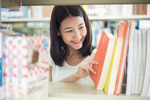 Asian college student seaching book for reseach in library.