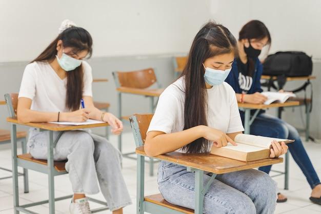 학교로 돌아온 아시아 대학생들은 마스크를 쓰고 교실에서 거리를 두고 공부한다