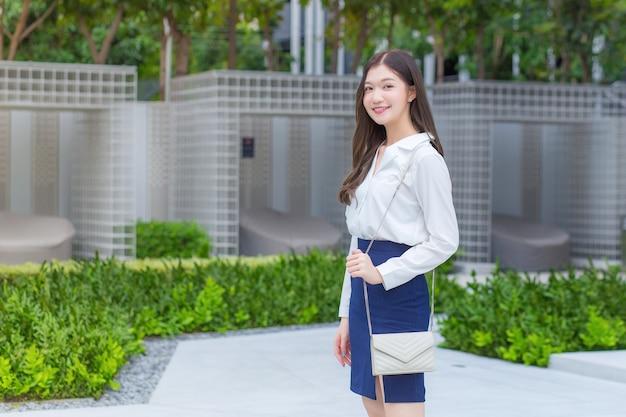 Азиатская уверенная деловая женщина носит белую рубашку и улыбается, идя на работу