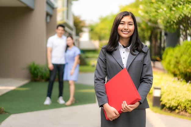 Asian confident woman real estate agent or realtor in suit holding red file and smile with young couple home sellers behind in front of house.
