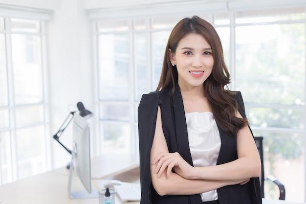 긴 머리에 검은 양복을 입은 자신감 넘치는 아시아 여성이 집에서 일하는 동안 서서 팔짱을 끼고 있습니다.