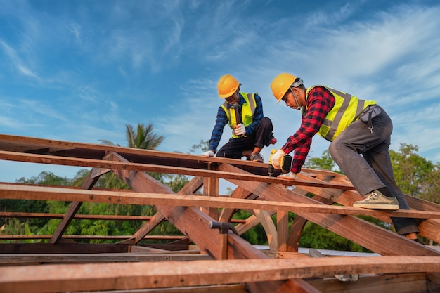 Asian construction worker install new roof, roofing tools, electric drill used on new roofs of wooden roof structure, teamwork construction concept.