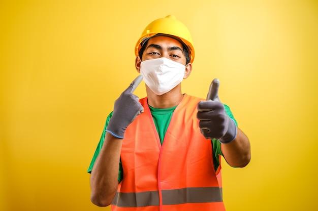보호 마스크와 안전한 헬멧을 가리키는 아시아 건설 노동자는 노란색 배경에 대해 건강과 안전을 우선시하도록 초대합니다