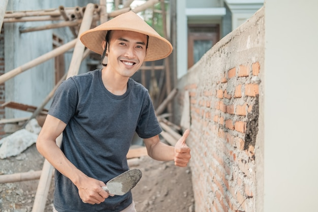 Asian construction worker smile at the camera wearing a cap with a thumbs up while holding the scoop