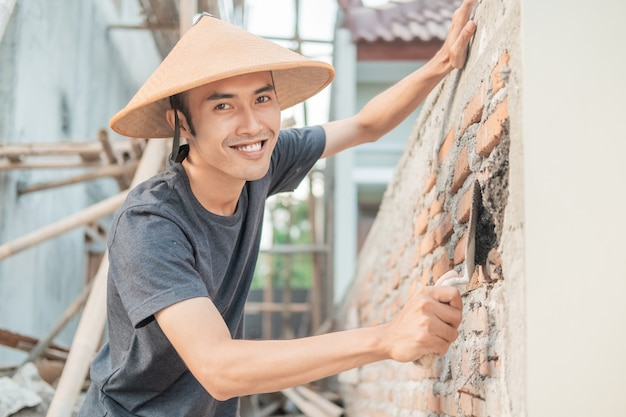 Asian construction worker smile at the camera wearing a hat while using a scoop to spread the cement on the bricks