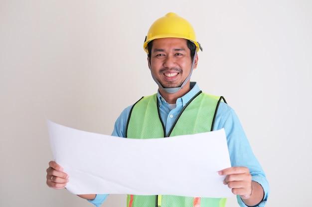 건물 설계 용지를 들고 웃고 있는 아시아 건설 노동자