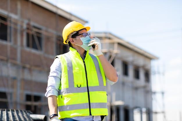 建築現場でトランシーバーで話しているアジアの建設労働者。コロナウイルスとインフルエンザの流行中にサージカルマスクを着用する
