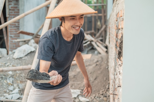 Asian construction worker using a scoop to attach cement to the bricks in an unfinished house