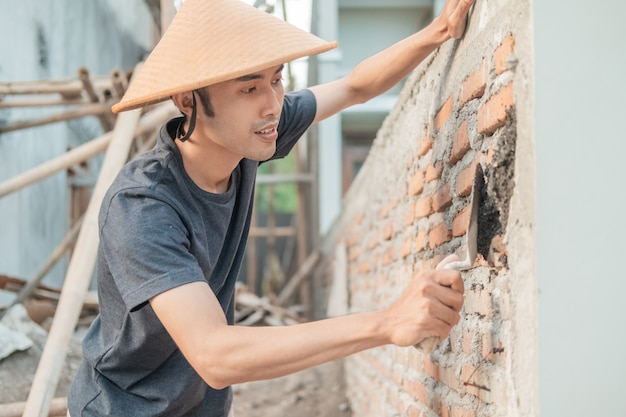 Asian construction worker using a scoop to spread the cement on the bricks