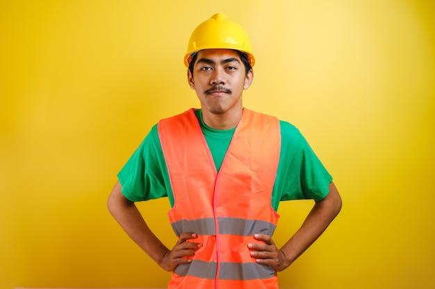 단단한 모자와 안전 조끼를 입은 아시아 건설 노동자는 노란색 배경에 대해 양손을 허리에 대고 카메라를 바라보며 미소를 짓고 있습니다. 남자는 자신감 있는 제스처를 보여