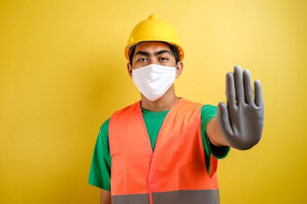 노란색 배경에 대해 정지 제스처를 만드는 보호 마스크를 쓴 아시아 건설 노동자