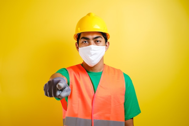 노란색 배경에 대해 누군가를 선택하는 앞으로 제스처를 가리키는 보호 마스크를 쓴 아시아 건설 노동자