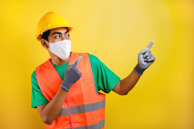 Asian construction worker wearing protective mask pointing isomething in his side against yellow background