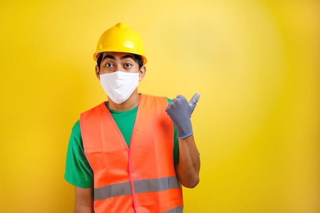 노란색 배경에 대해 옆구리에 무언가를 가리키는 보호 마스크를 쓴 아시아 건설 노동자