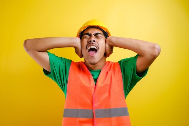 보안 헬멧을 쓰고 제복을 입은 아시아 건설 노동자는 시끄러운 음악 소리에 짜증이 난 표정으로 손가락으로 귀를 덮고 있습니다. 청각 장애인 개념입니다.