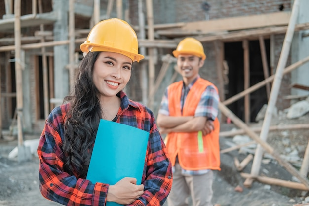 Asian construction worker woman smiles at the camera wearing a safety helmet against the background of a male contractor s