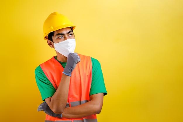 노란색 배경에 대해 아이디어를 찾는 보호 마스크를 쓴 아시아 건설 노동자