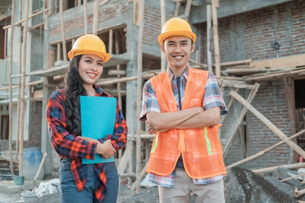 Asian construction workers wearing vests and safety helmets outdoor