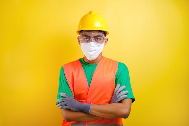마스크와 안전 고글을 쓴 아시아 건설 노동자 남자는 노란색 배경에 자신감 있는 몸짓으로 팔을 구부렸다