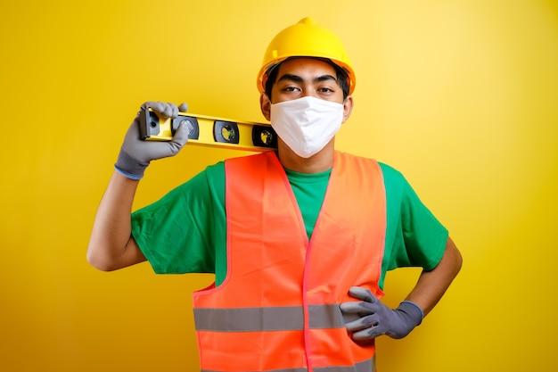 마스크와 안전 조끼를 입은 아시아 건설 노동자 남자는 자신감 있는 몸짓으로 어깨에 수로를 들고 있습니다. 노란색 배경에 대한 작업 개념 준비