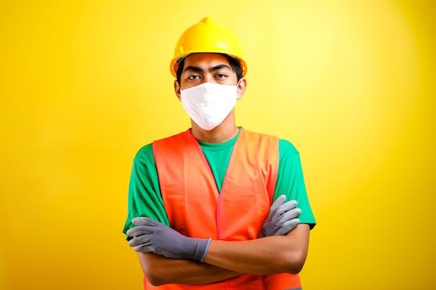 마스크와 안전 조끼 스탠드를 가진 아시아 건설 노동자 남자는 노란색 배경에 대한 자신감 제스처와 함께 그의 팔을 구부렸다