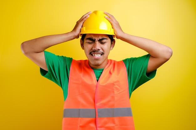 안전모를 쓴 아시아 건설 노동자 남자는 머리에 손을 대고 스트레스를 받고 수치심과 놀란 얼굴에 충격을 받고 화나고 좌절했습니다. 실수에 대한 두려움과 분노.