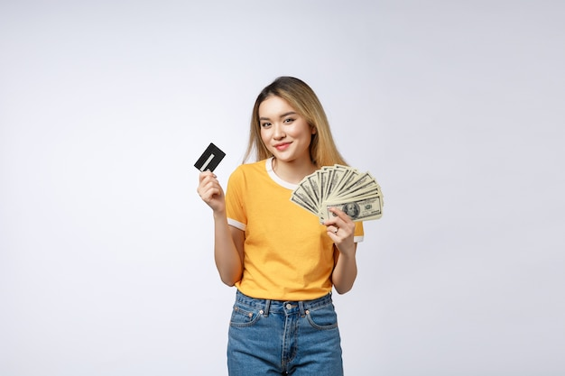 お金のドル紙幣とクレジットカードのファンを保持しているアジアのコンテンツの女性