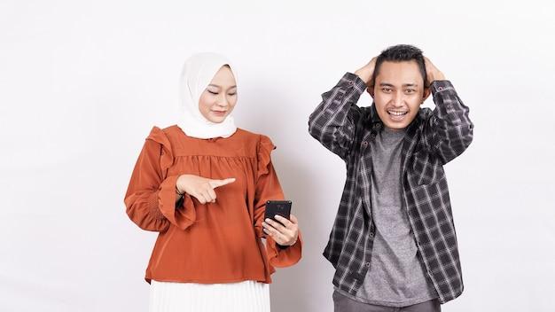 Азиатская пара мальчик раздражено выражение и девушка держит телефон