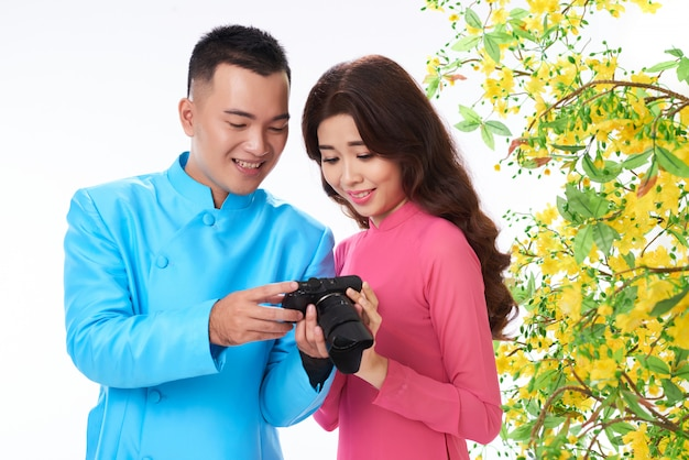 Asian couple in bright traditional attire checking photos on camera next to blooming mimosa
