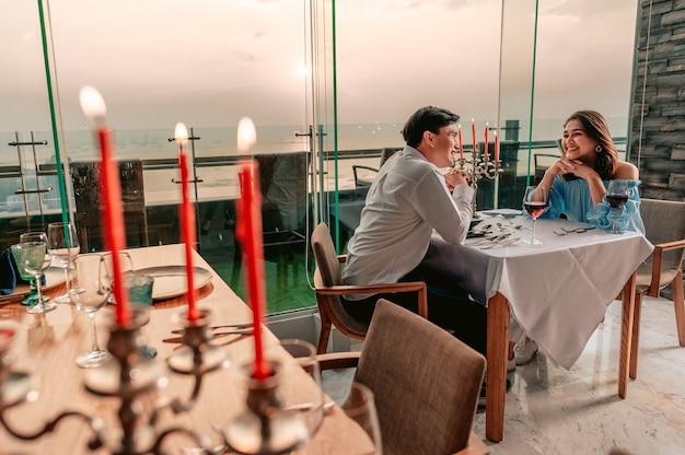 アジアのカップルはレストランhotelvacationdinnerのテーブルでロマンチックな景色と楽しくおしゃべりします