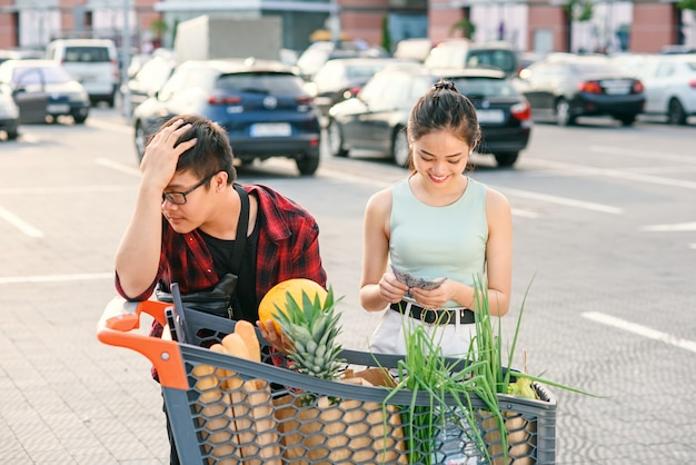 Asian couple checking their shopping cart full of healthy organic food on the background of big store.