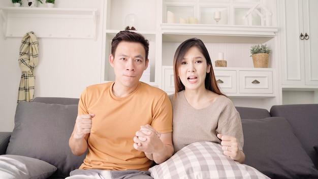 アジアのカップルが自宅のテレビのリビングルームの前でサッカーの試合を応援