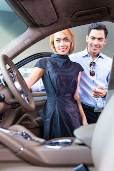 インテリアを見て自動車販売店で高級車を選ぶアジアのカップル