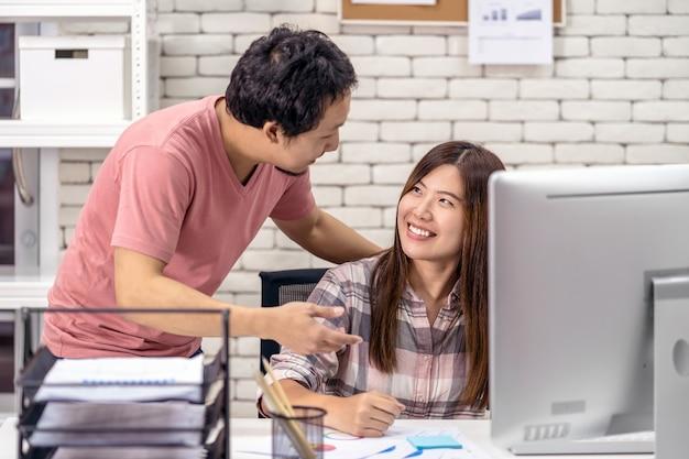 現代のオフィスでテクノロジーコンピューターと一緒に働くアジアのカップルの同僚