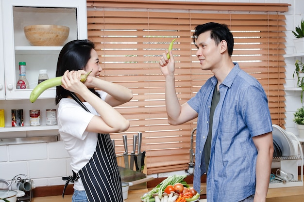 Asian couple cooking together in the kitchen at home have fun playing with each other. the concept of starting a family. living during the coronavirus pandemic. social distancing