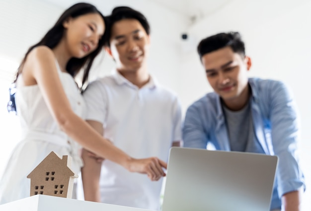 Asian couple decide to buy a new house from laptop with real estate agent, subject is a house model with key