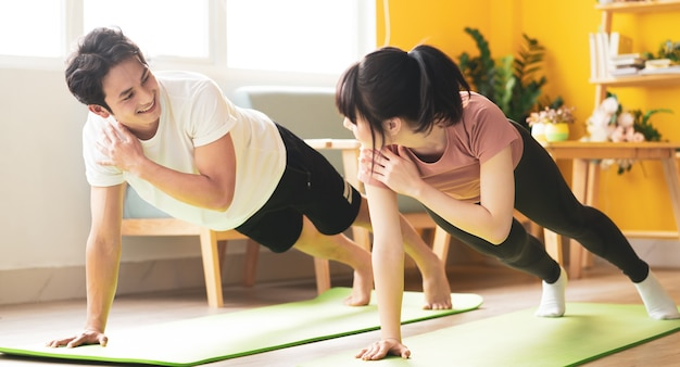 Asian couple doing exercise together at home