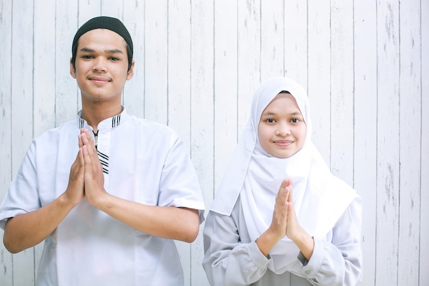 Азиатская пара делает мусульманское рукопожатие в камеру для поздравления с праздником ид аль-фитр