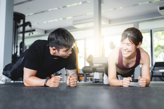 Asian couple doing push-ups in gym.