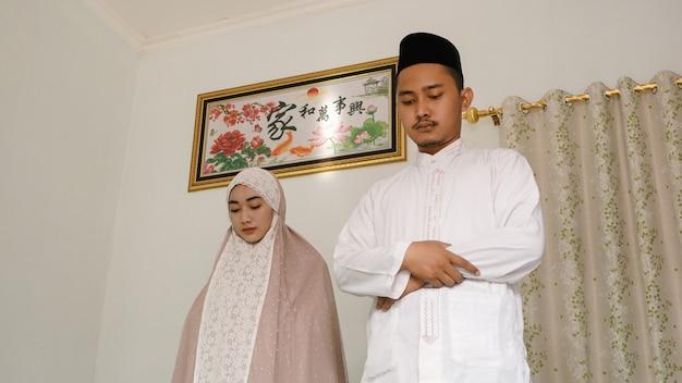Азиатская пара поклоняется вместе дома